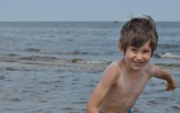 sätta på land den lyckliga ferieillustrationen för den klädda flickan som liten leka sjömanhavsvektor Familj med barn på stranden Arkivfoto