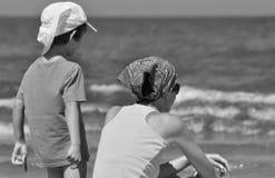 sätta på land den lyckliga ferieillustrationen för den klädda flickan som liten leka sjömanhavsvektor Familj med barn på stranden Royaltyfri Foto