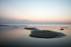 Sätta på land efter solnedgången med sand och moln arkivbilder