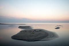 Sätta på land efter solnedgången med sand och moln arkivfoto