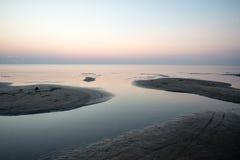 Sätta på land efter solnedgången med sand och moln arkivbild