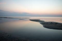 Sätta på land efter solnedgången med sand och moln arkivfoton