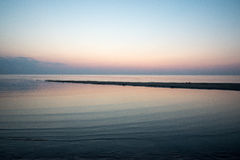 Sätta på land efter solnedgången med sand och moln royaltyfri foto