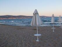 Sätta på land i skymning med strandstolar och paraplyer Fotografering för Bildbyråer
