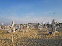 Sätta på land i soluppgång med strandstolar och paraplyer Arkivfoto