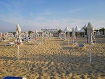 Sätta på land i soluppgång med strandstolar och paraplyer Arkivfoton