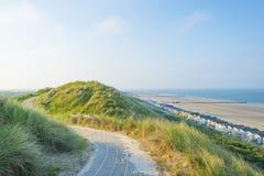 Sätta på land kabiner längs bergiga dyn på en fritids- strand i vår arkivfoto