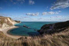 Sätta på land kusten av Dorset, England på sommardag med blå himmel Royaltyfri Fotografi