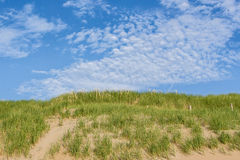 Sätta på land kusten med dyn på en solig dag med några härliga moln Royaltyfri Foto