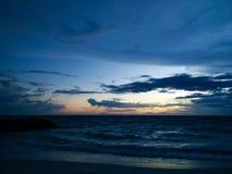 Sätta på land landskapet på solnedgången med molnig himmel Arkivbild