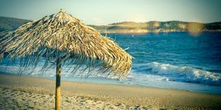 Sätta på land med paraplyet för stranden för solparaplyer - kallbegrepp Royaltyfria Bilder