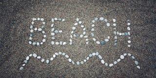 Sätta på land ordet och vinka symbolet på sanden - tonat foto Arkivfoto