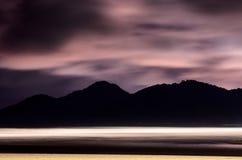 Sätta på land på natten med sand, havsvågor och berg Royaltyfri Bild
