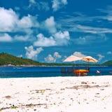 Sätta på land på Seychellerna med picknicktabellen och stolar Arkivbilder