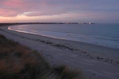 Sätta på land på solnedgången med stadljus i avstånd Arkivfoto