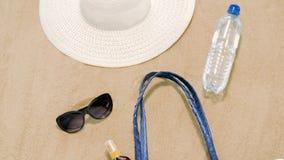 Sätta på land påsen, sunscreen, solglasögon och hatten på sand stock video