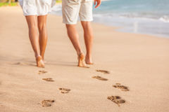 Sätta på land par som barfota går på sand - fotspår royaltyfri fotografi