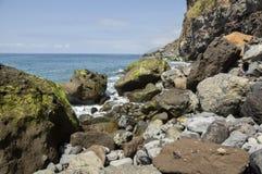 Sätta på land Ponta de Solenoid den steniga gröna kustlinjen med klippor och stora vulkanstenar, madeiraön, Portugal Arkivbild