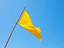 Sätta på land säkerhet som varnar den gula flaggan med blå himmel Arkivfoto