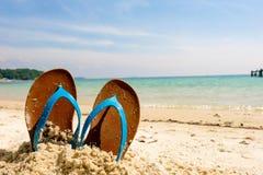 Sätta på land sandaler på det sandiga havet, semesterloppsymbol Arkivfoto