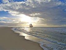 Sätta på land, seglingskeppet, havet och solnedgången Arkivbild