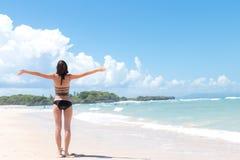 Sätta på land semestern Lycklig kvinna som tycker om solig dag på stranden Öppna armar, frihet, lycka och salighet Tropiskt begre arkivbild