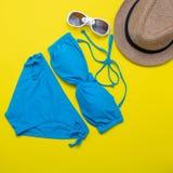 Sätta på land tillbehör på den gula bakgrunden - solglasögon, bikini, badskor och randig hatt Sommar är det kommande begreppet arkivbild