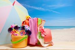 Sätta på land tillbehören, hatten, solglasögon, skor, paraply på trä, begrepp Royaltyfria Bilder
