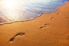 Sätta på land, vågen och fotspår på solnedgångtid Arkivfoton