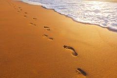 Sätta på land, vågen och fotsteg på solnedgångtid royaltyfria bilder