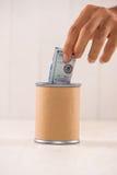 Sätta pengar in i donation boxas Donera begreppet arkivfoto
