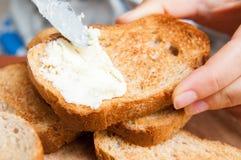Sätta smör på rostat bröd Fotografering för Bildbyråer