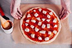 Sätta stycken av mozzarellaen på pizza Arkivbilder