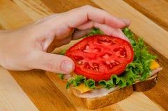Sätta tomaten på kalkonsmörgåsen Royaltyfri Fotografi