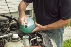 Sätta vindrutetorkarevätska i en bil Arkivbild