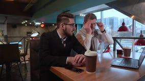 Sätter den vuxna mannen för två coworkers på exponeringsglas, och med hans unga coworker diskuterar ett projekt med en bärbar dat stock video