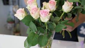 Sätter den yrkesmässiga blomsterhandlaren för kvinnan rosor på vasen i blomsterhandeln, handcloseup lager videofilmer