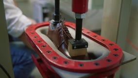 Sätter märkes- skor för produktion, förlagen skodon i pressen Skodonproduktion vid mänskliga händer Skofabrik lager videofilmer