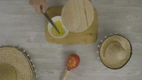 Sätter mat i maträtten med en kniv På tabellen är de två mexicanska hattarna, maracas, abstraktionen för instagram lager videofilmer