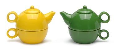 Sätze der gelben und grünen keramischen Teekannen und der Becher Stockfotos