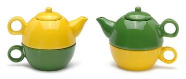 Sätze der gelben und grünen keramischen Teekannen und der Becher Stockfotografie