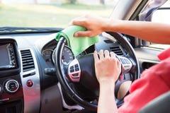 Säubern des Autoinnenraums mit grünem microfiber Stoff lizenzfreie stockfotos