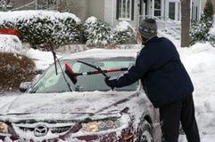 Säubern des Autos nach Winterschneesturm stockbild