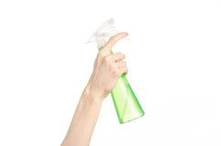 Säubern des Haus- und Reinigerthemas: die Hand des Mannes, die eine grüne Sprühflasche für das Säubern lokalisiert auf einem weiß lizenzfreie stockfotos