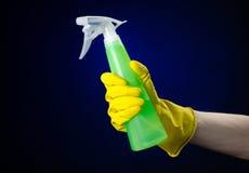 Säubern des Haus- und Reinigerthemas: die Hand des Mannes in einem gelben Handschuh, der eine grüne Sprühflasche für das Säubern  Stockbilder