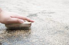 Säubern eines Bodens im Freien in einem Hausbereich durch das Bürsten mit einem bru Stockfotos