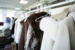 Säubern Sie die Kleidung, die an den Aufhängern an der chemischen Reinigung hängt Stockfotografie