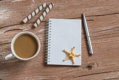 Säubern Sie leeren Notizblock, Plätzchen, Tasse Kaffee, Starfish Reise- und Wochenendenhintergrund Freier Platz für Text Lizenzfreie Stockfotografie
