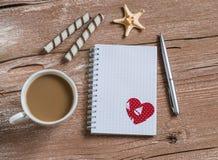 Säubern Sie leeren Notizblock, Plätzchen, Tasse Kaffee, Starfish und rotes Papierherz Stockfoto
