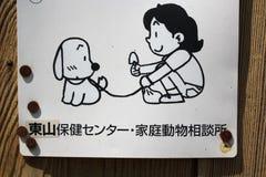 Säubern Sie, nachdem Ihr Hund herein Japaner unterzeichnen Stockfotos